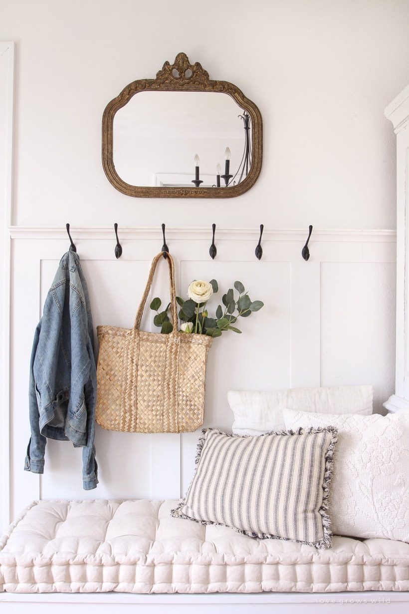 Entryway with white walls, and mirror, and black coat hooks.