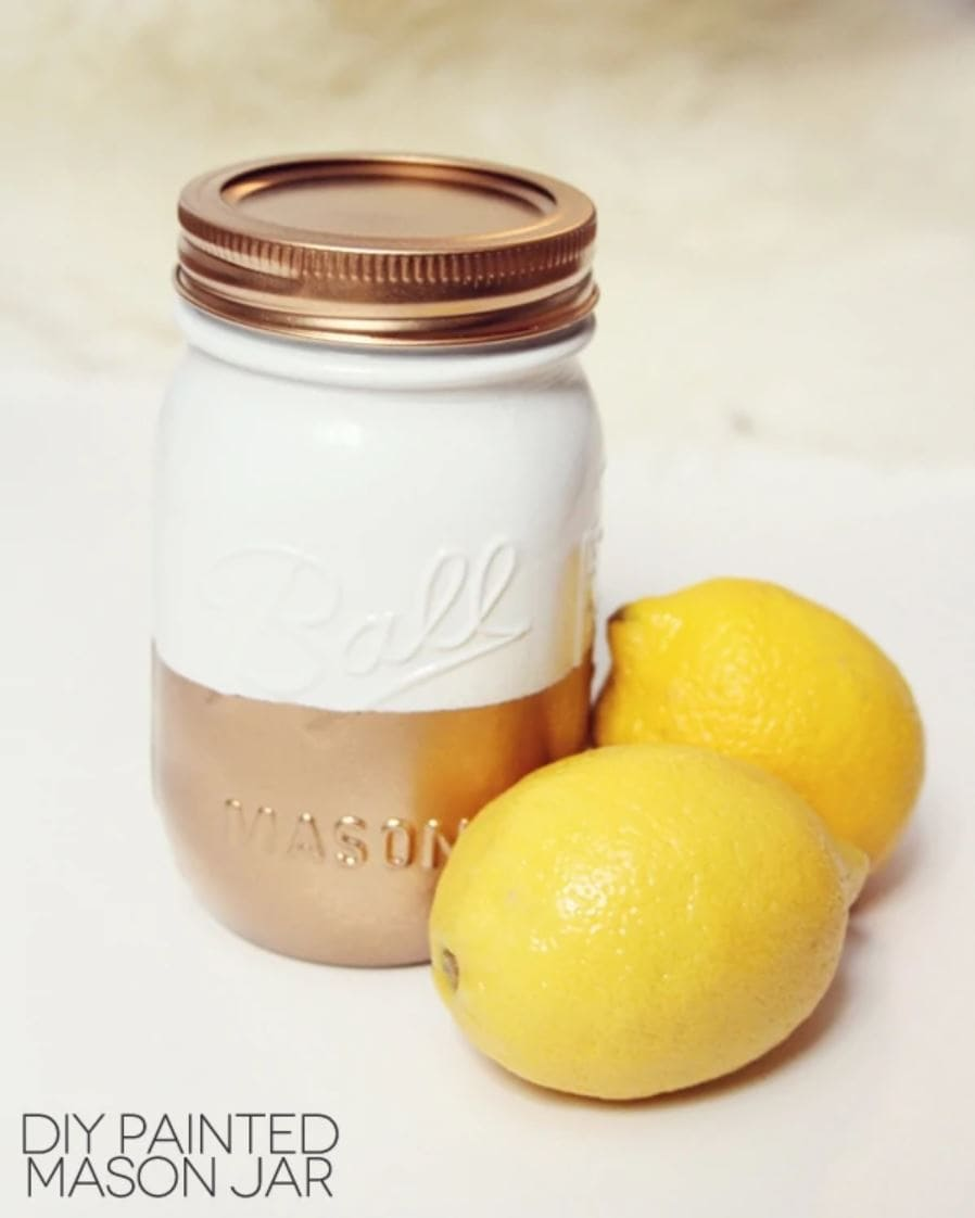 A mason jar painted with gold on the bottom and white on the top.