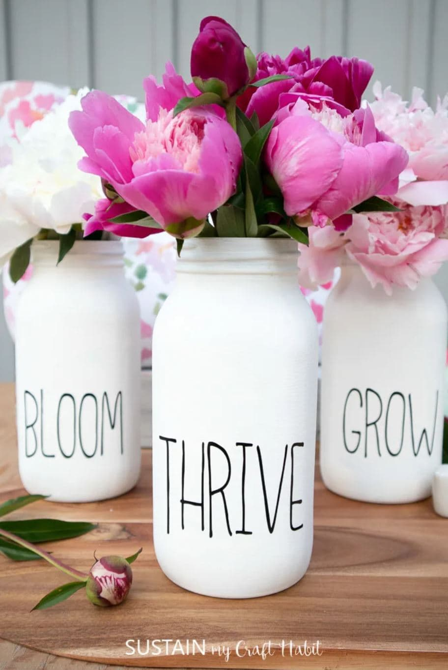 """Three white painted mason jars with the words, """"bloom"""", """"thrive"""", and """"grow"""" on them."""