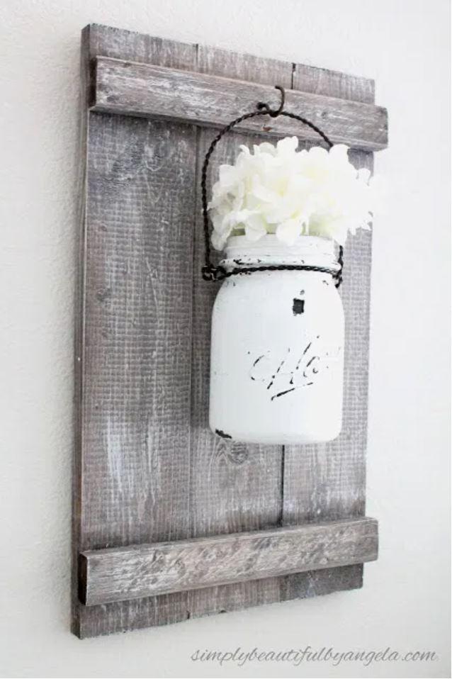 A mason jar sconce on a rustic wooden board.