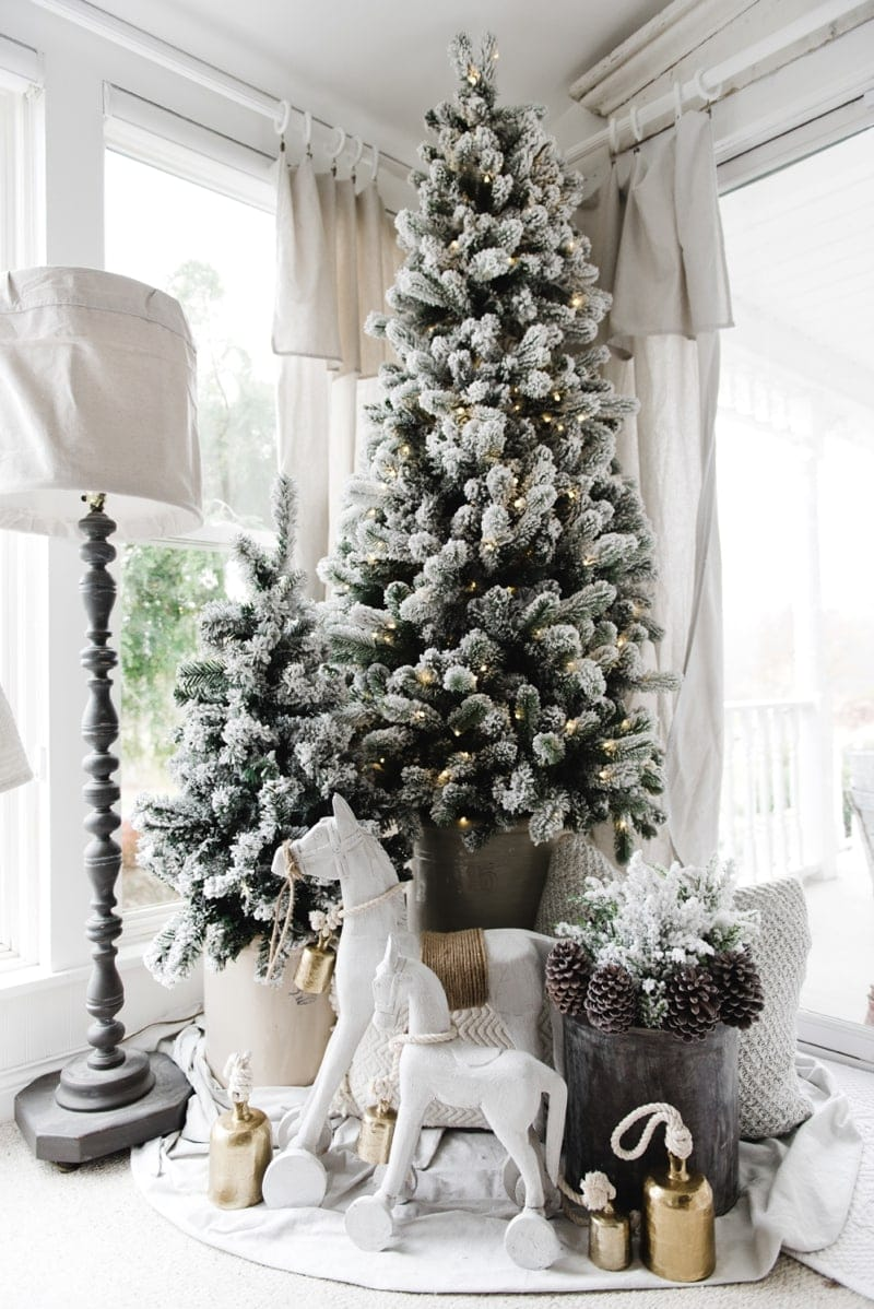Chalk-painted white rocking horses in front of a flocked Christmas tree.