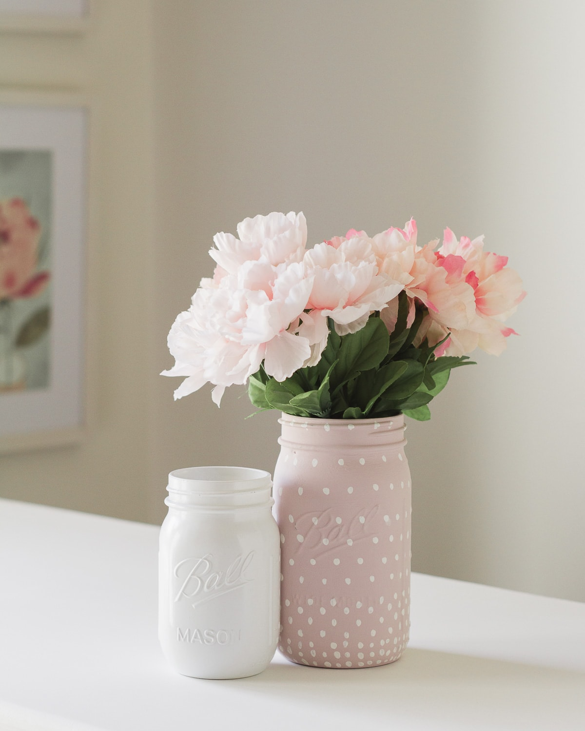 A white painted mason jar and a pink (with white polka dots) mason jar with flowers inside.