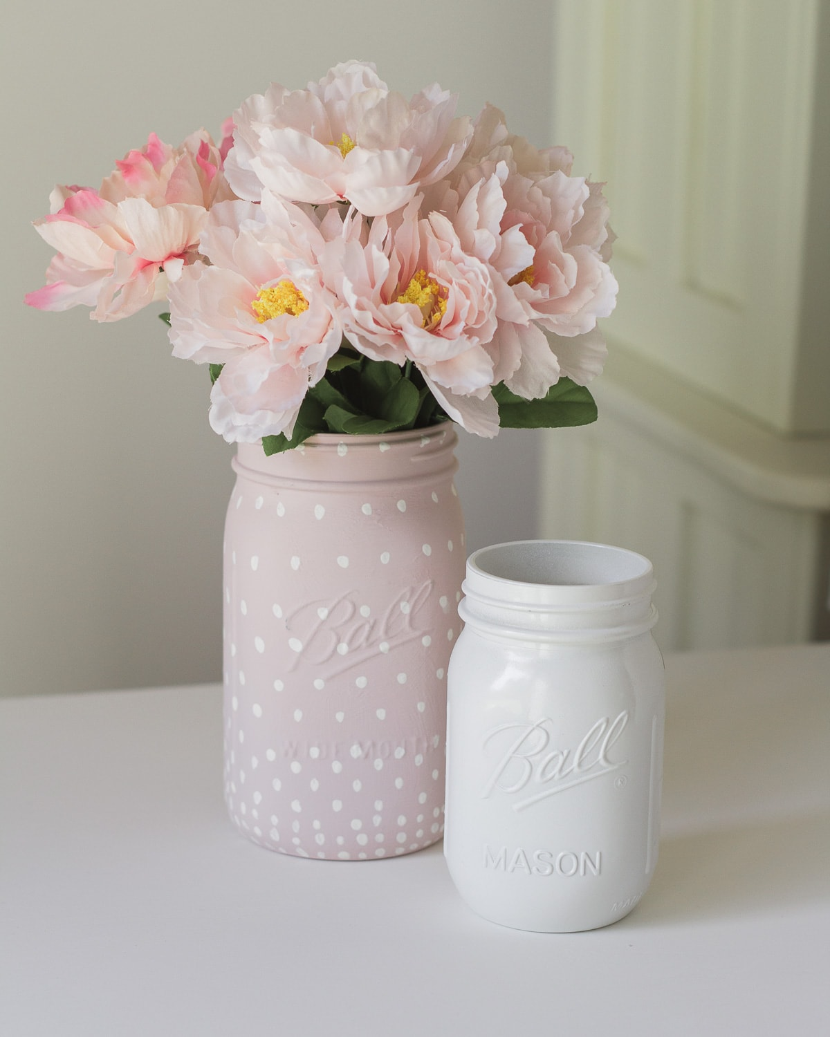 Painted mason jars with flowers inside.