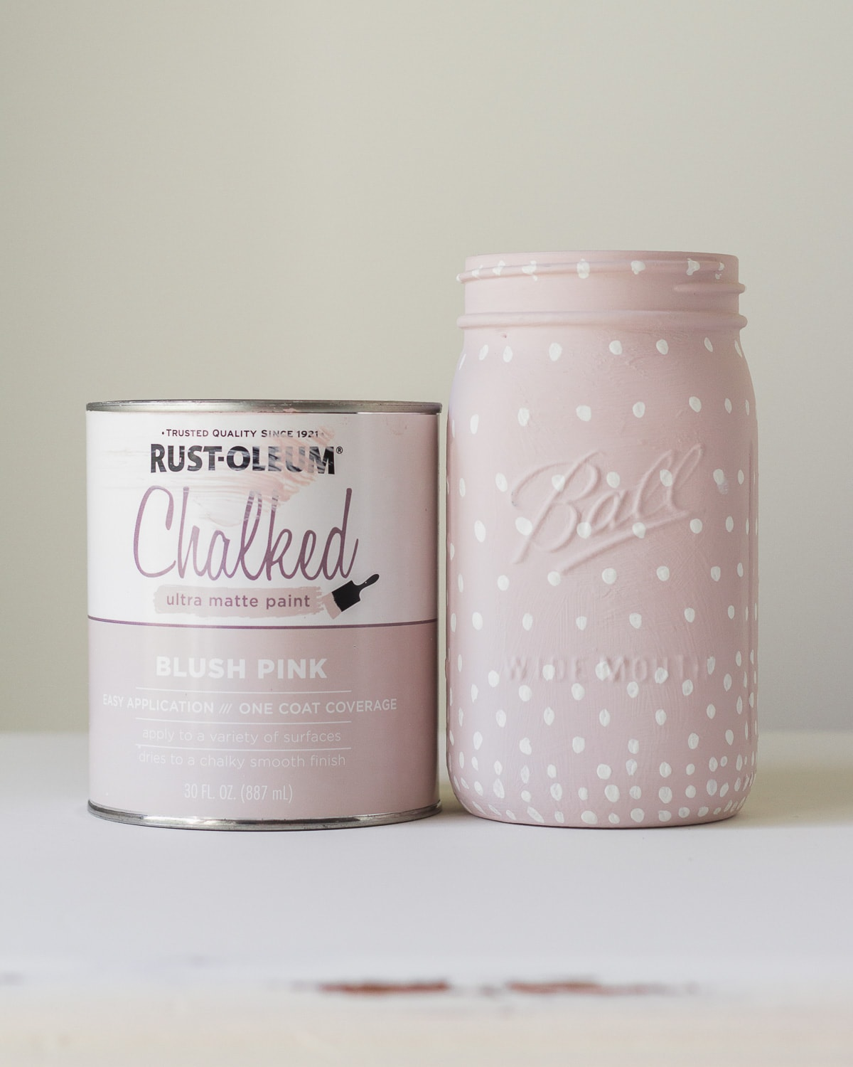 A can of Rust-Oleum chalked paint in Blush Pink and a glass jar painted with the paint, plus white polka dots.