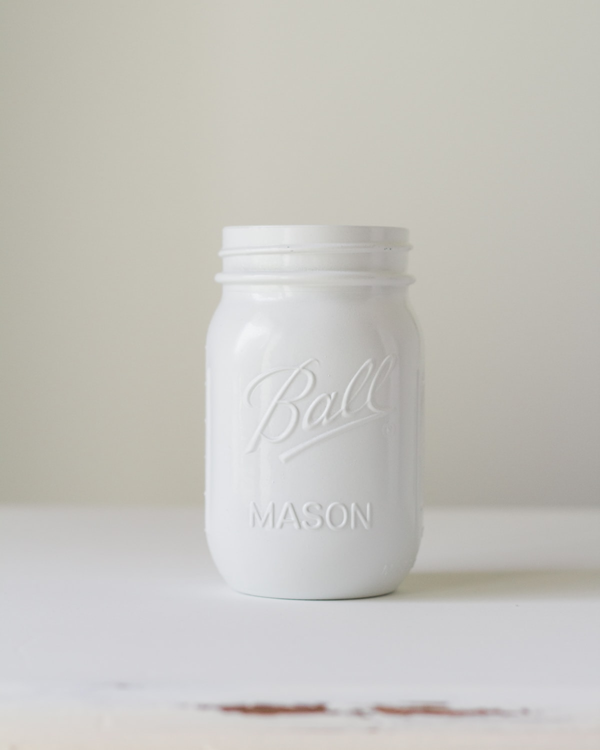 A Ball Mason Jar painted with glossy white spray paint.