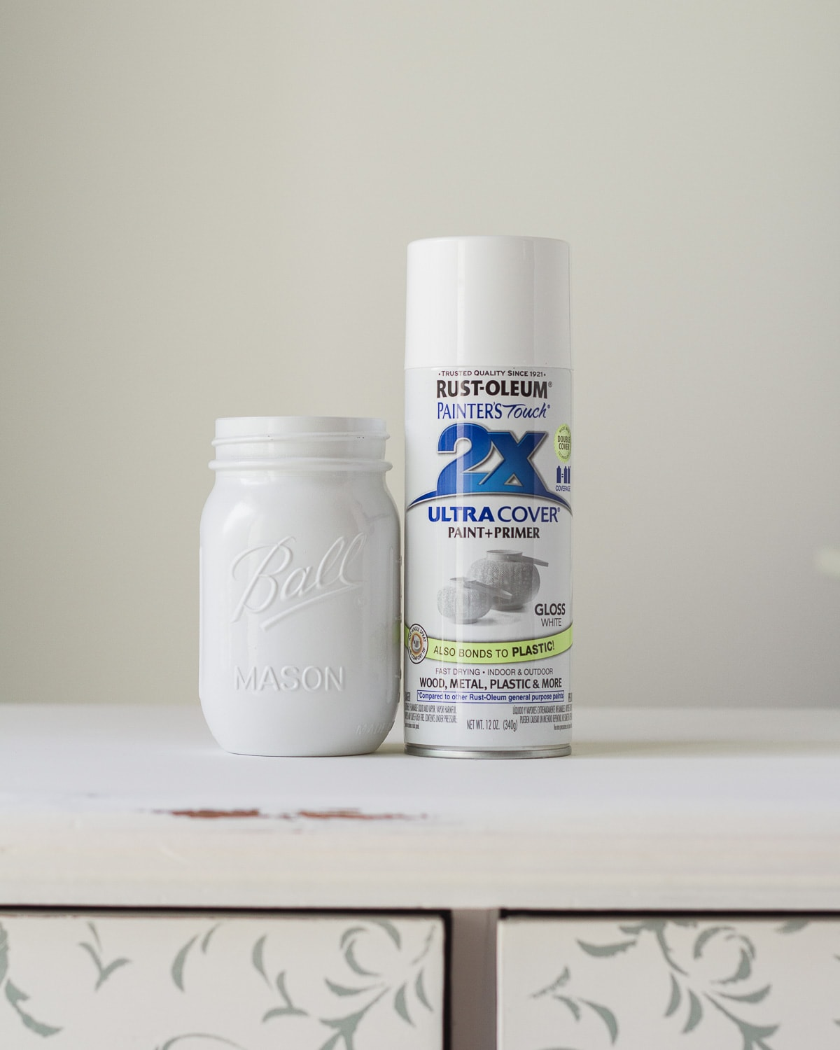 A painted mason jar and a can of glossy spray paint.