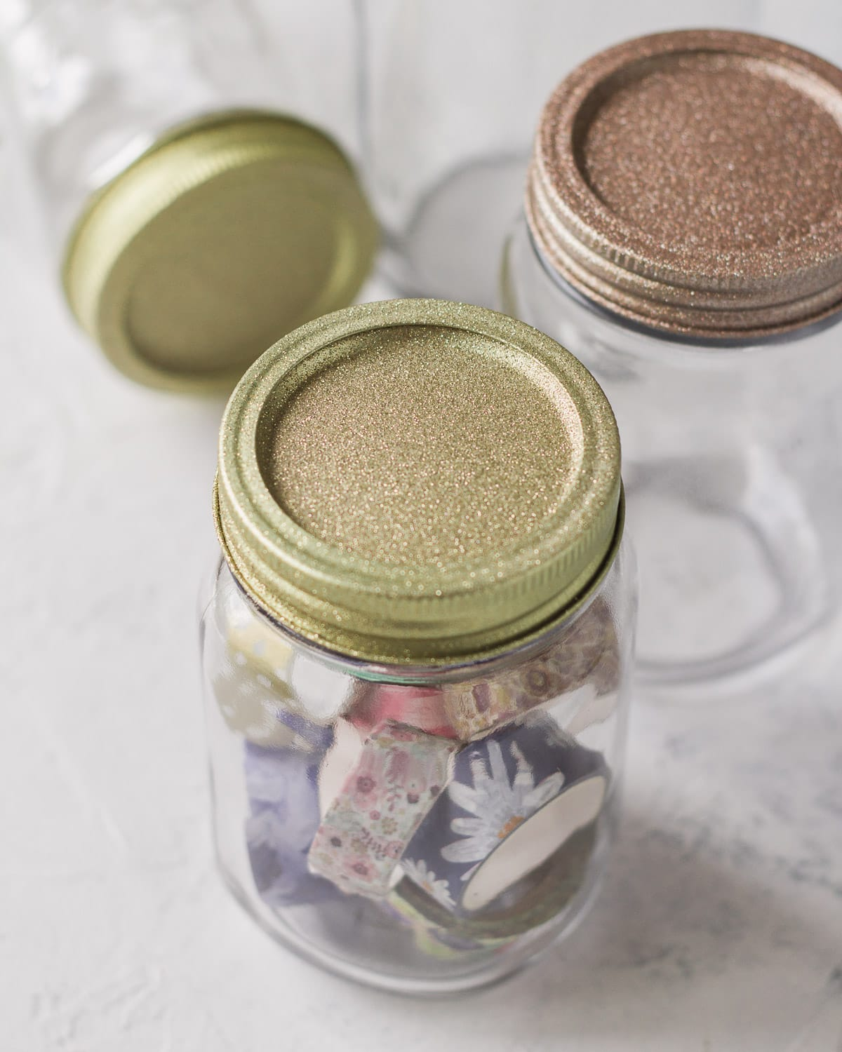 Mason jars topped with glittery lids in gold and rose gold.