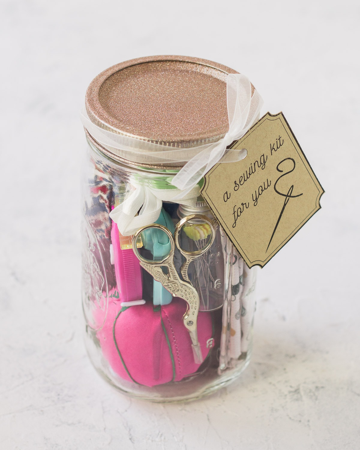 A mason jar sewing kit topped with a glittery lid.