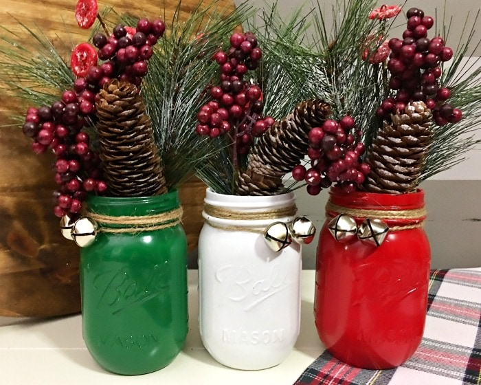 Three mason jars spray painted in green, white, and red with Christmas décor inside.