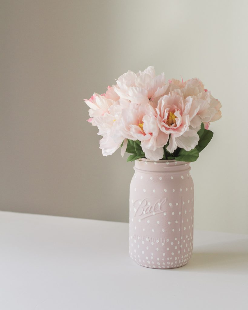 A painted glass jar filled with pink faux flowers.