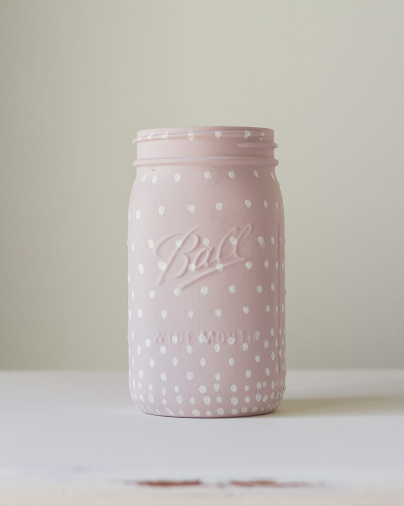 A ball mason jar painted pink with white polka dots.