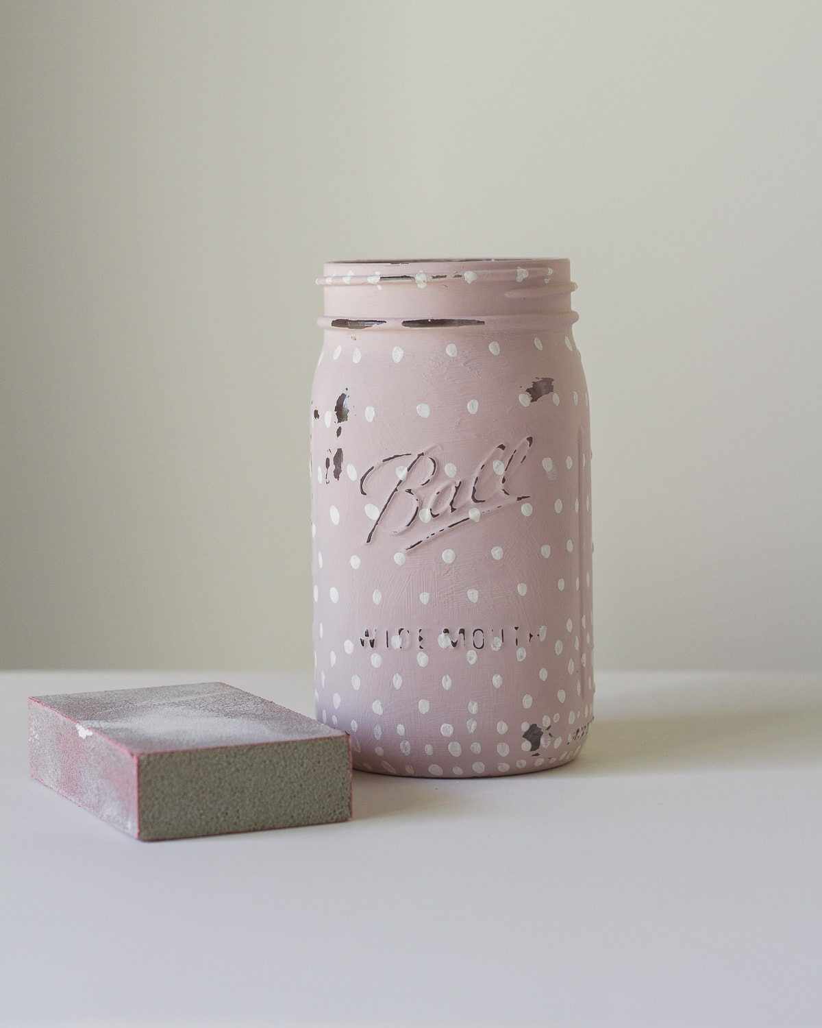A quart mason jar painted with pink chalk paint and white polka dots distressed with a sanding block.