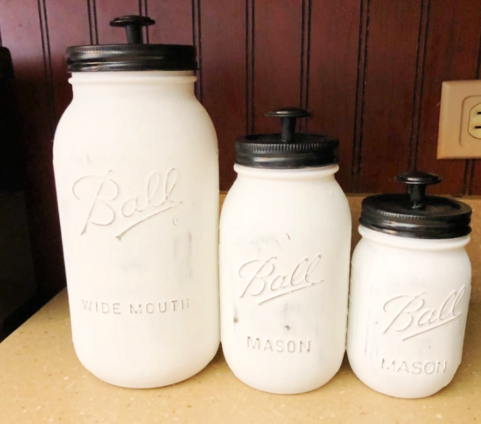 Three mason jars painted white and turned into canisters with the addition of knobs to the lids.