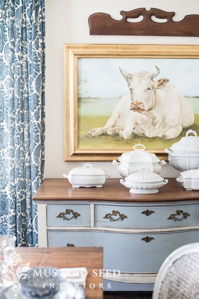 A painting of a cow and a blue dresser.