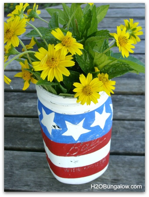 A stars and stripes mason jar with yellow flowers inside.