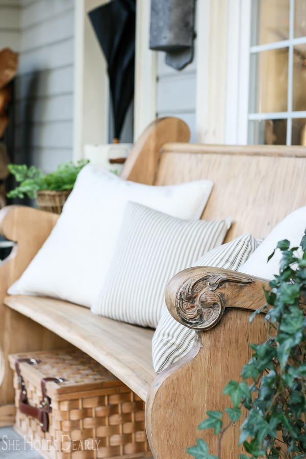 A vintage church pew on a porch with pillows.