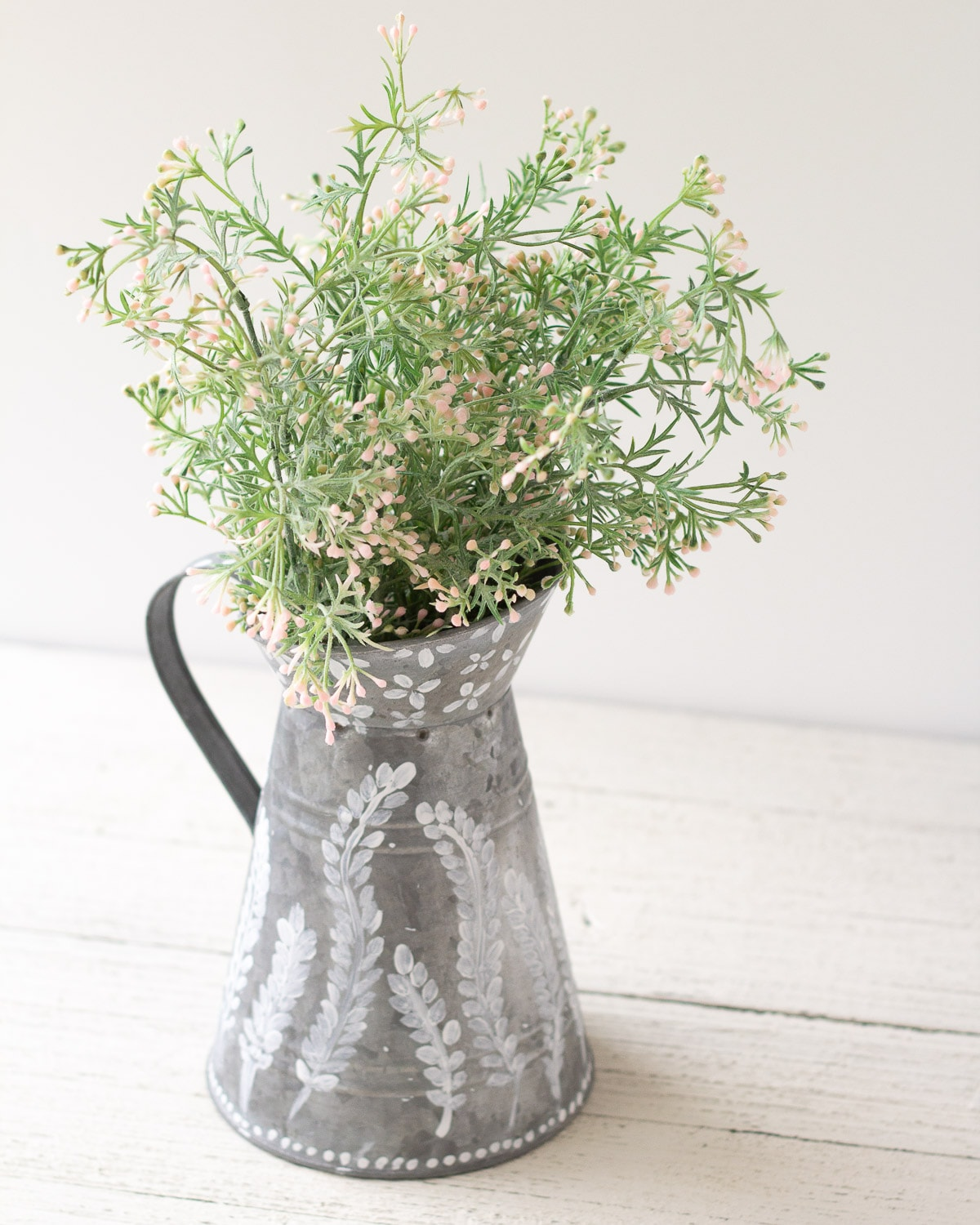 A galvanized pitcher filled with faux florals and decorated white paint floral designs.