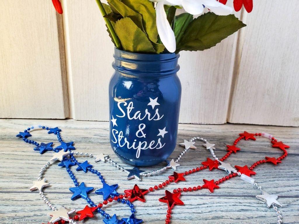 "A blue ""stars and stripes"" mason jar made with a Cricut."