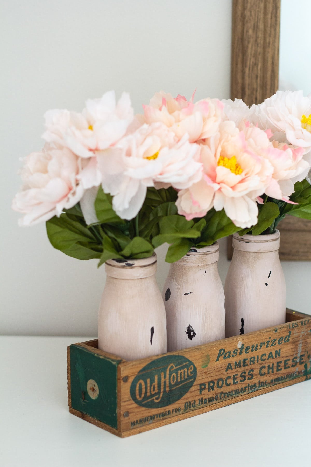 Faux flowers in vintage cheese crate.