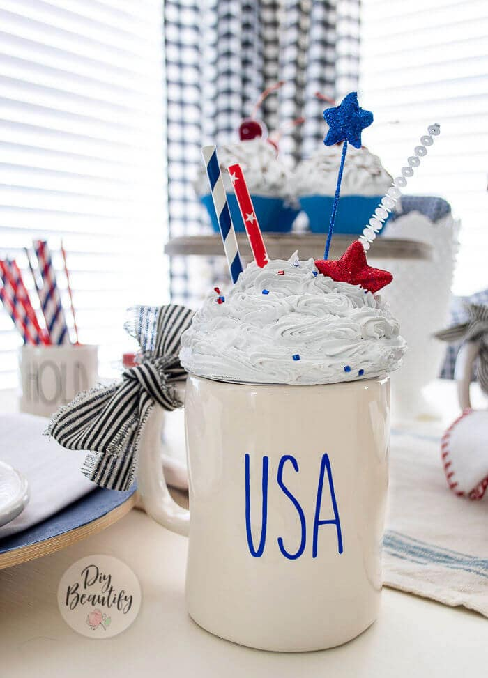 """A mug with """"USA"""" on the front and topped with a faux whipped cream topper."""