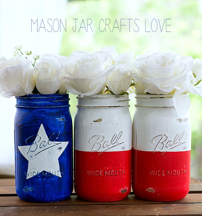 Mason jars filled with white flowers and painted to resemble a Texas flag.