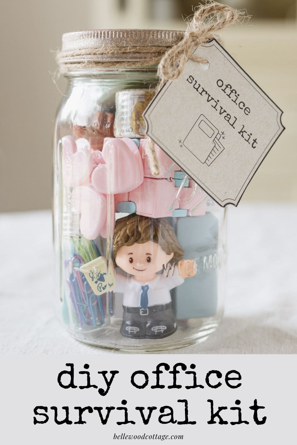 """A mason jar filled with office supplies and gift tag with the words, """"DIY Office Survival Kit"""" on the image."""