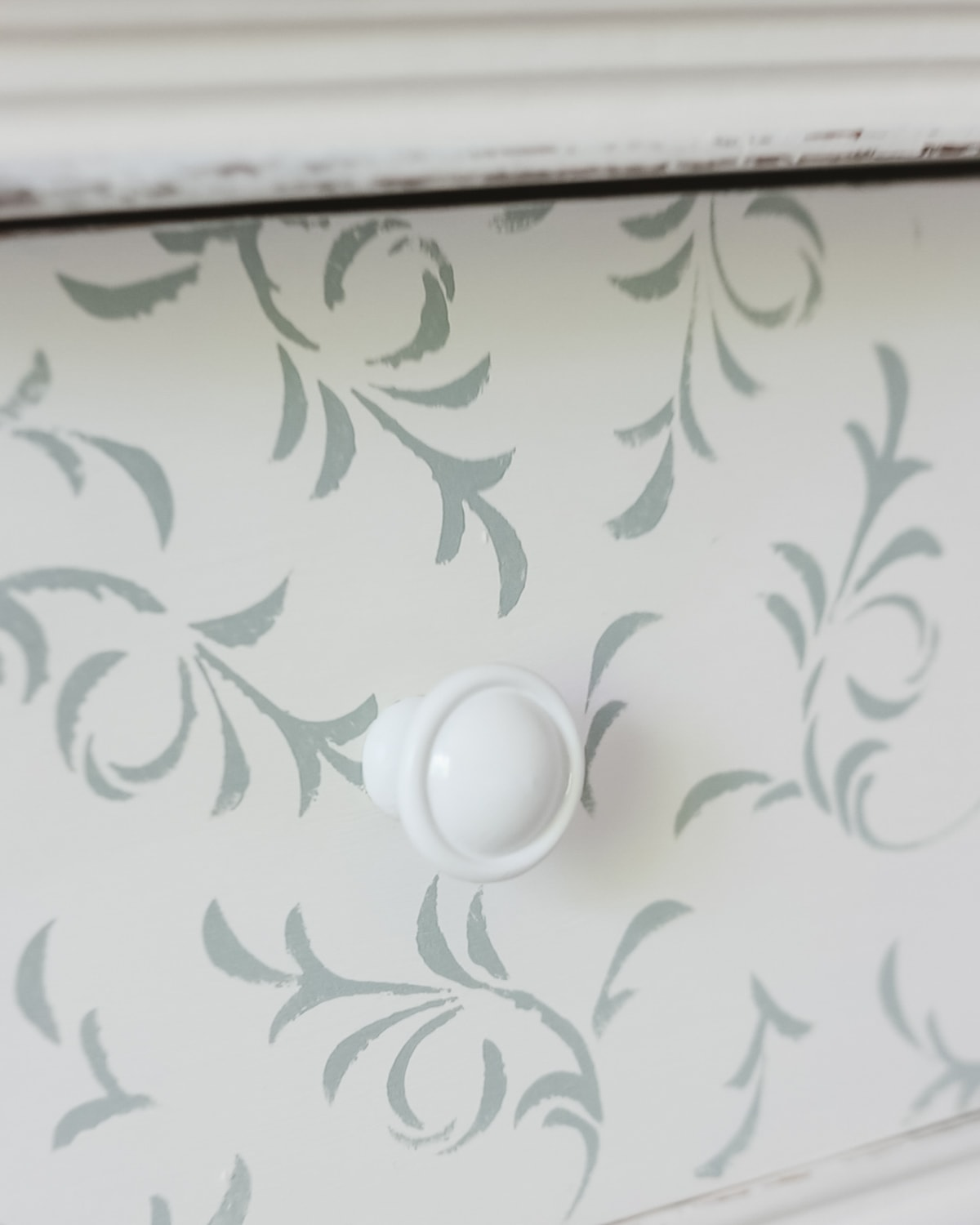 A close-up look at a knob spray-painted white and installed on a stenciled dresser.