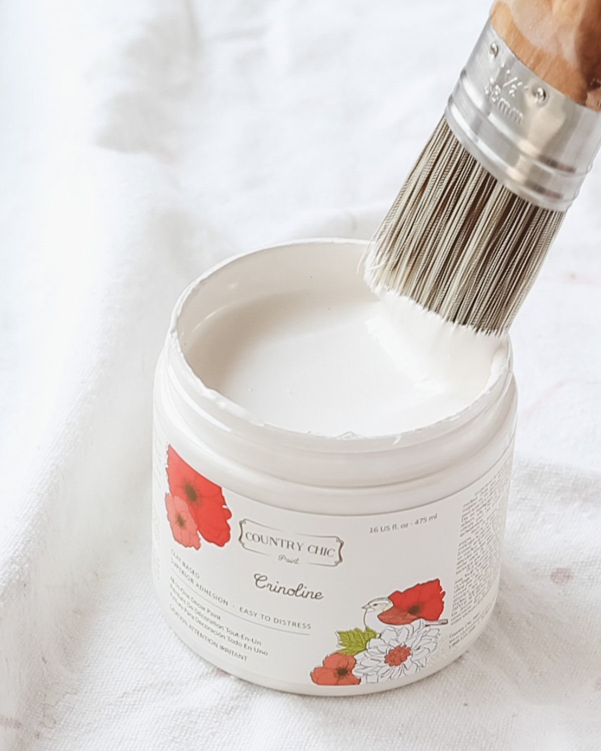 A paintbrush dipping into a can of paint.