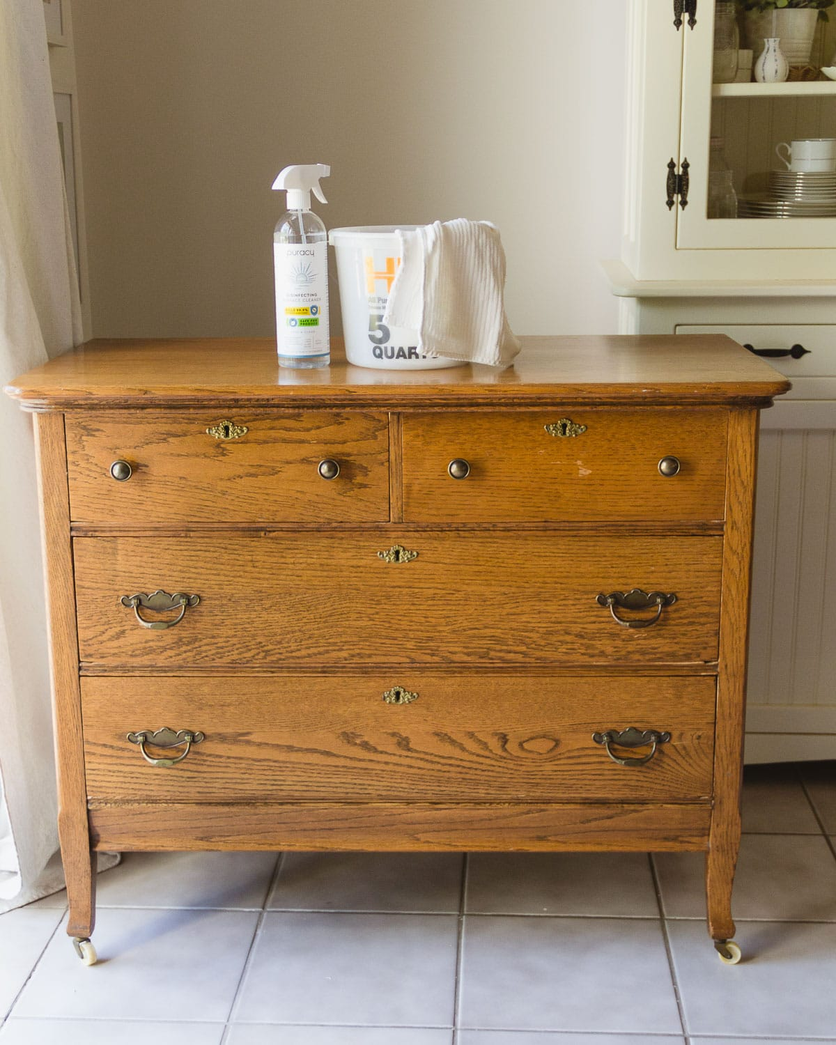 A vintage oak dresser with cleaning supplies on top of it.