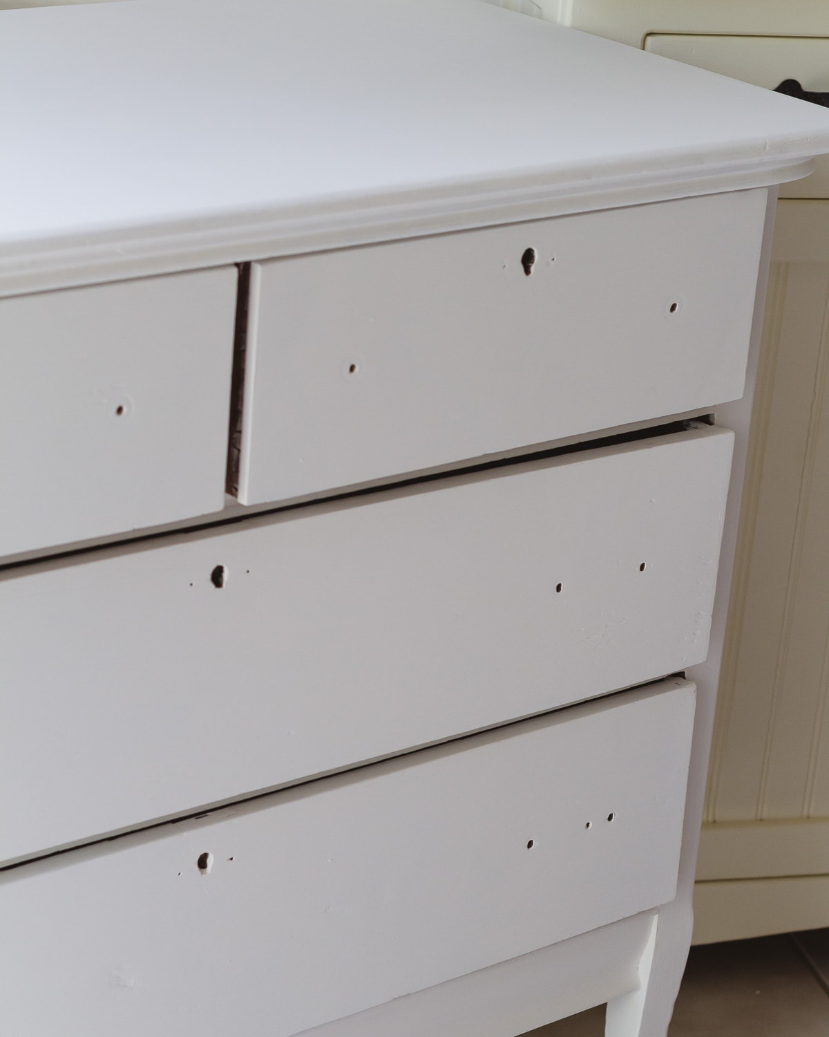 A vintage dresser painted white with the hardware removed.