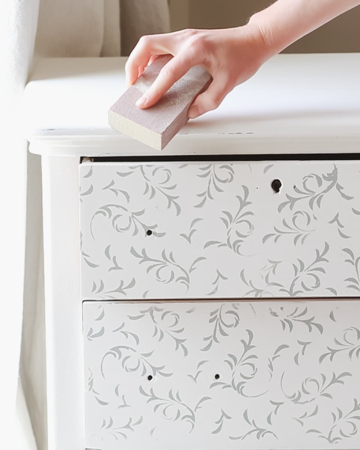Distressing a painted dresser with a sanding block.