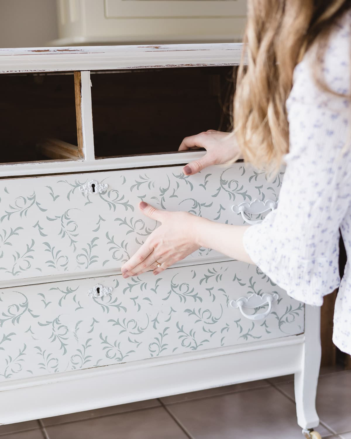 Inserting a drawer back into a painted dresser.