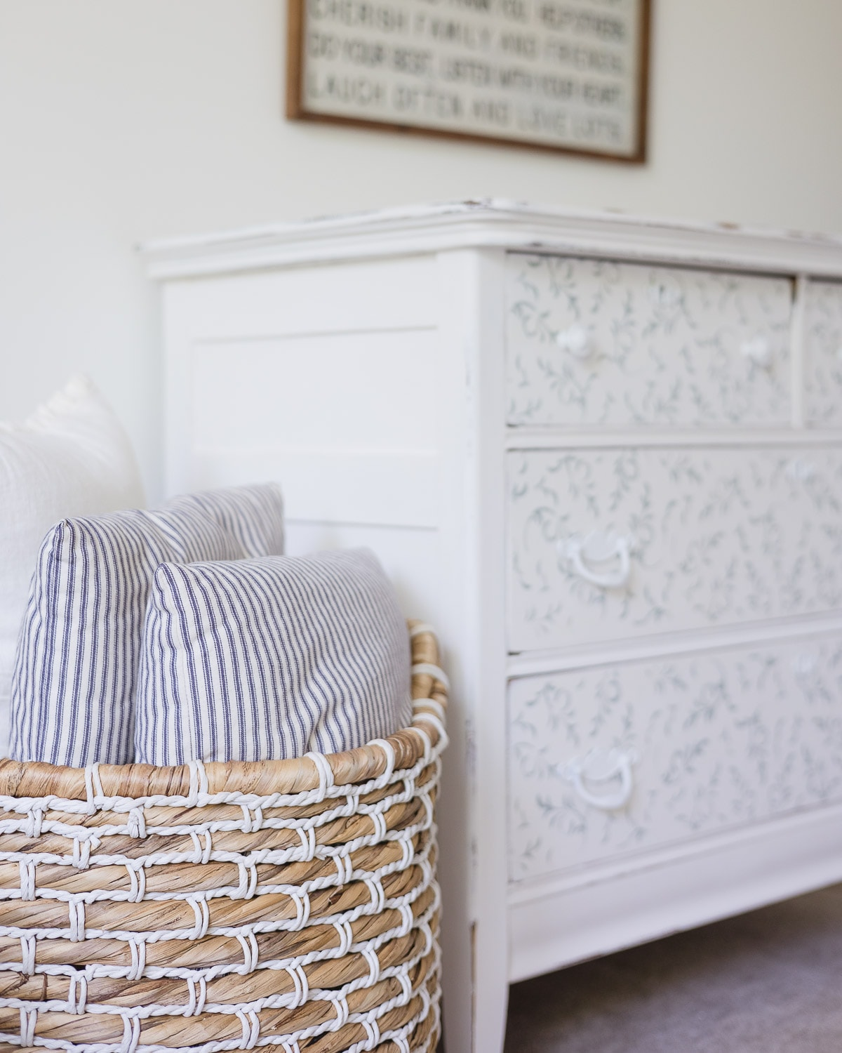 A woven basket with ticking pillows and a painted dresser in the background.