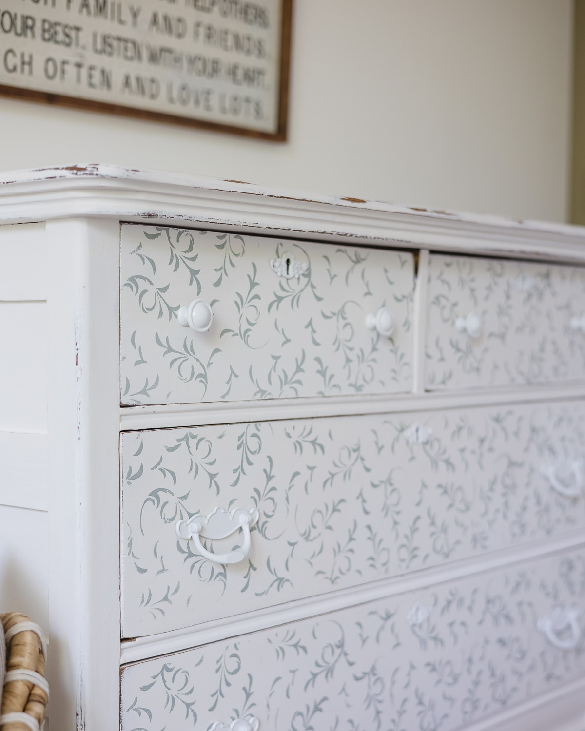 A vintage dresser painted white with blue floral stenciling and spray-painted white hardware.