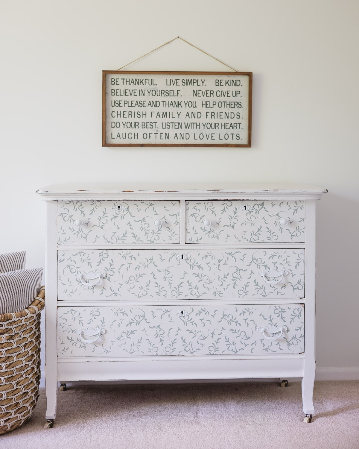 A stenciled white and blue dresser with inspirational farmhouse wall art hanging above it.