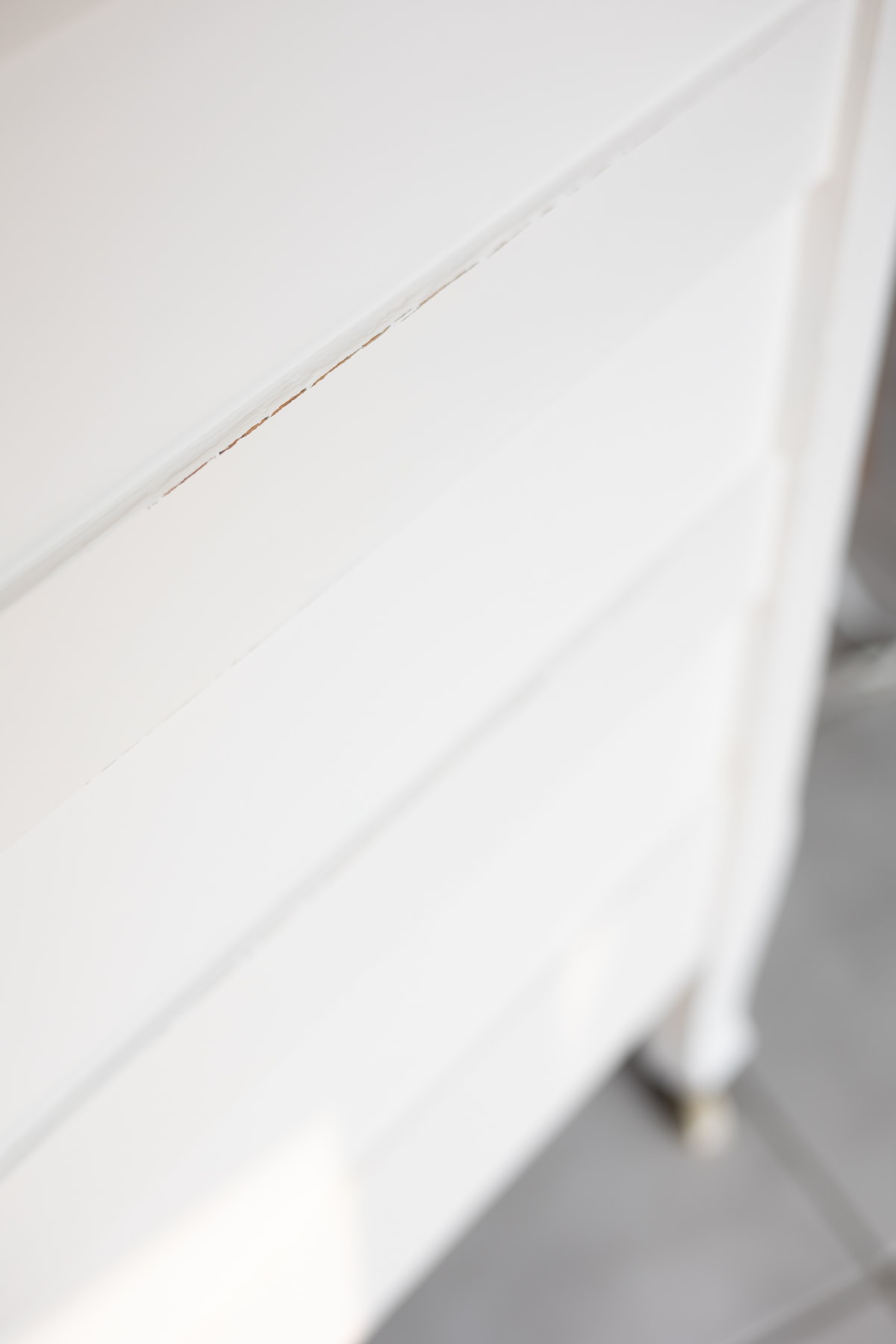 The side of a white dresser showing the difference between a waxed and an unwaxed finish.