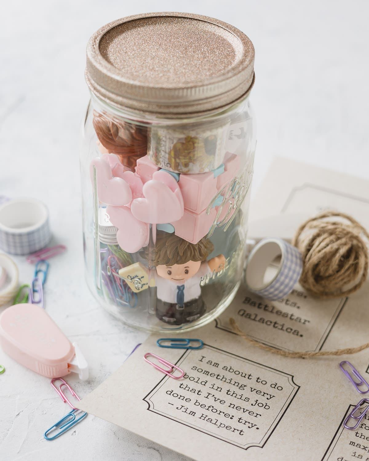 Gift tags, twine, washi tape, corrector tape, and other office supplies packed into a mason jar with a glittery lid.