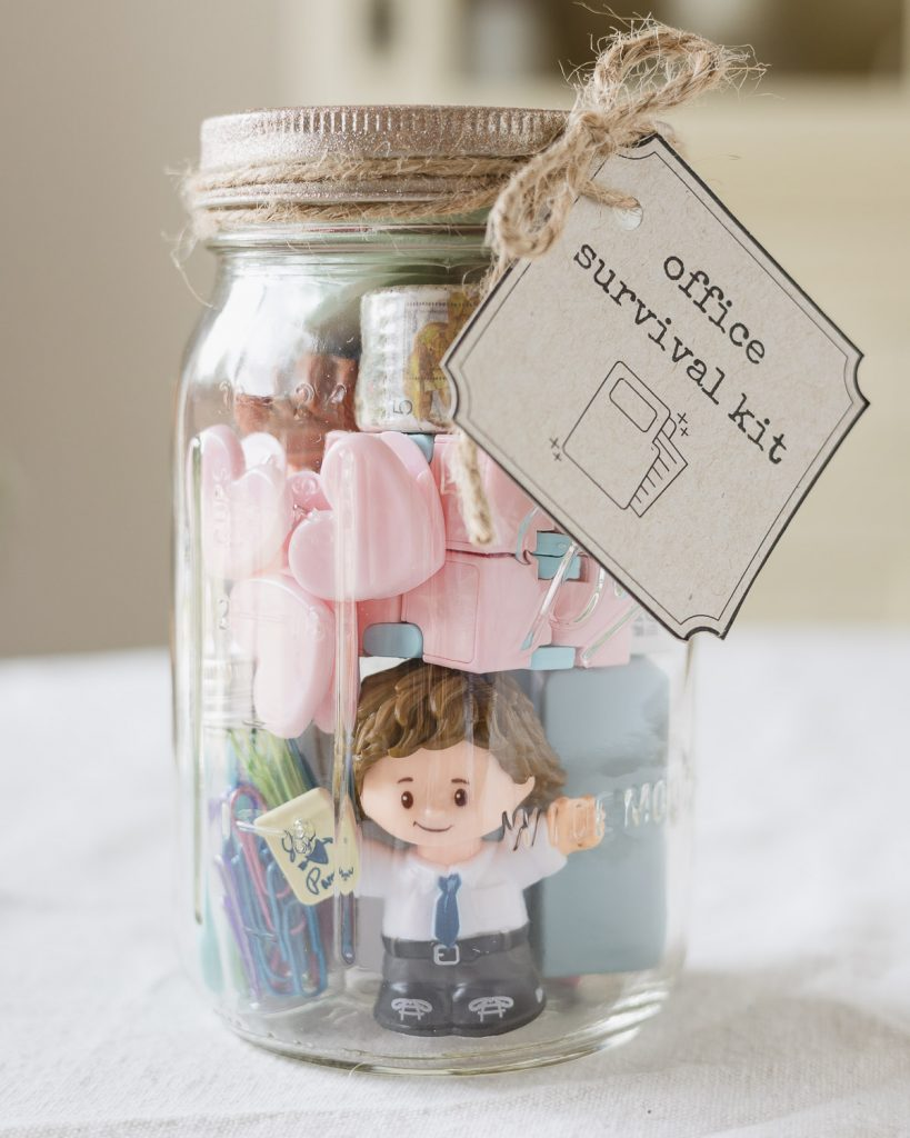 """A mason jar filled with office supplies, a """"Jim"""" figurine from The Office and a tag that reads, """"Office Survival Kit""""."""