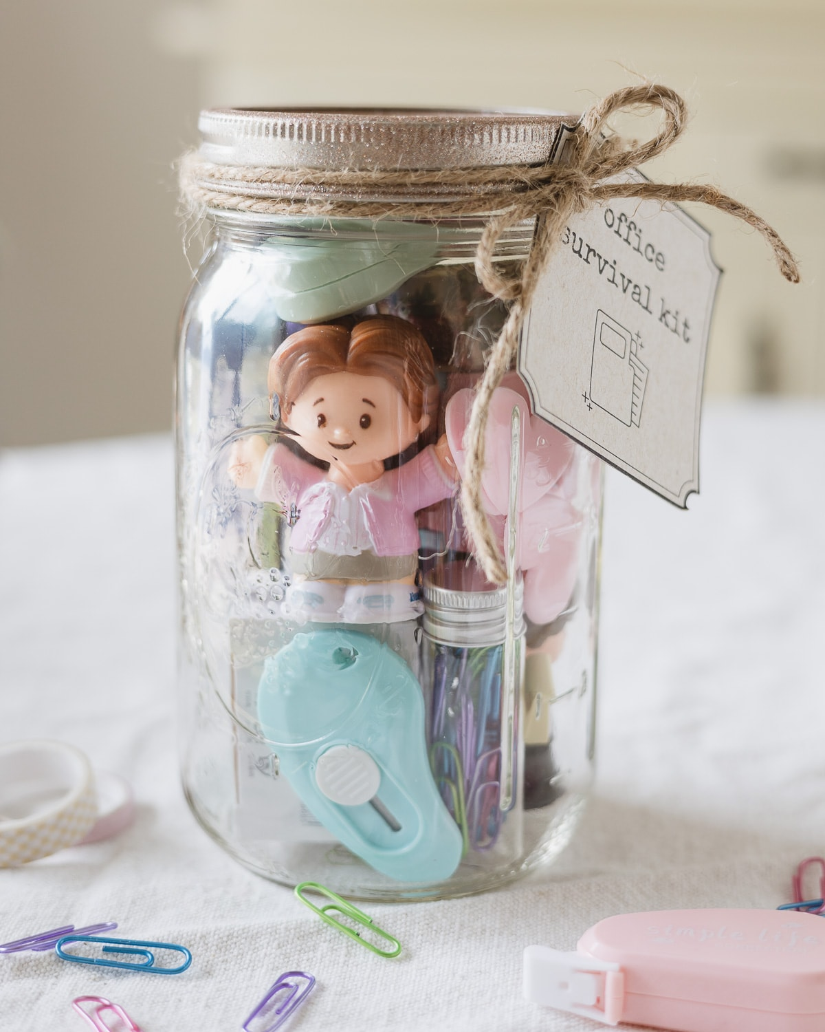 """A mason jar filled with office supplies, a """"Pam"""" figurine from The Office and a tag that reads, """"Office Survival Kit""""."""