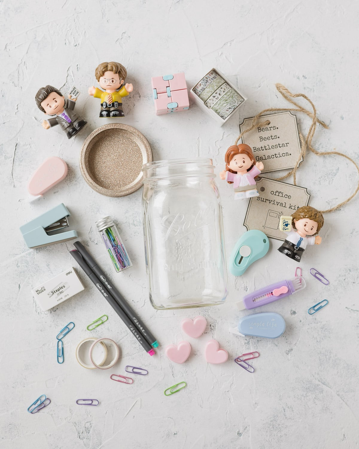 Paperclips, office supplies, Fisher Price Little People figures, and a mason jar.