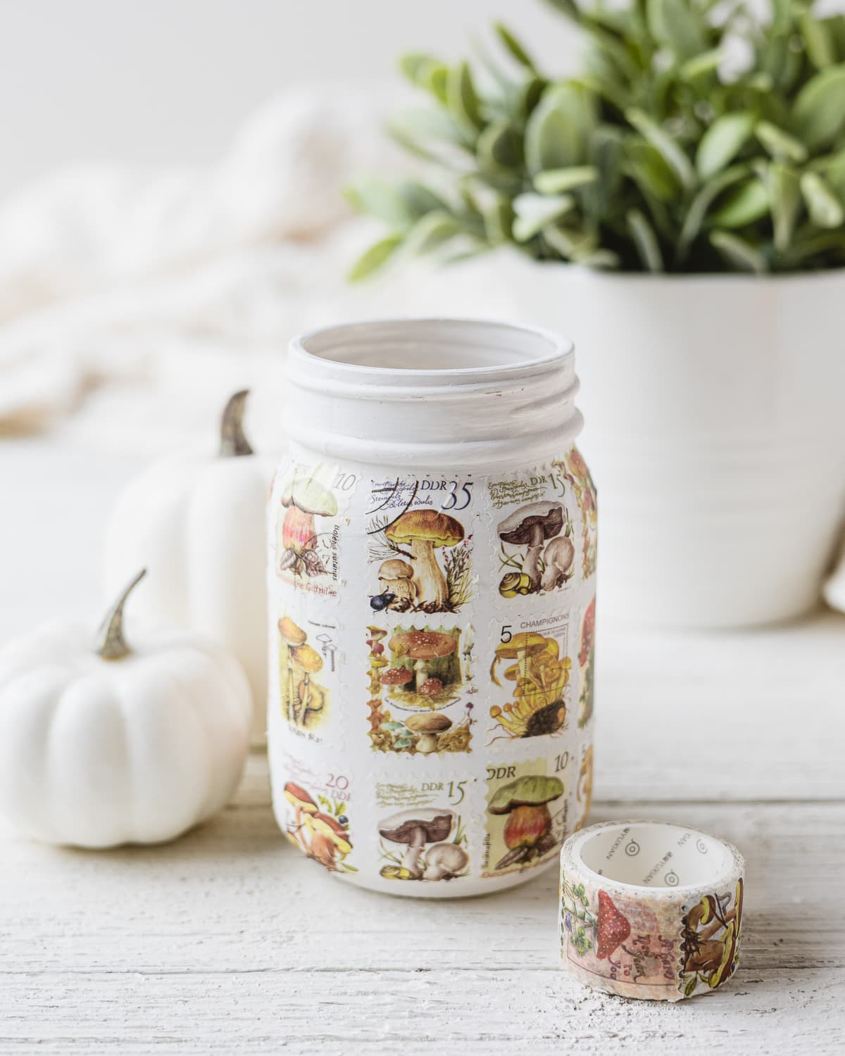 A mason jar painted white and covered with postage stamp washi tape.