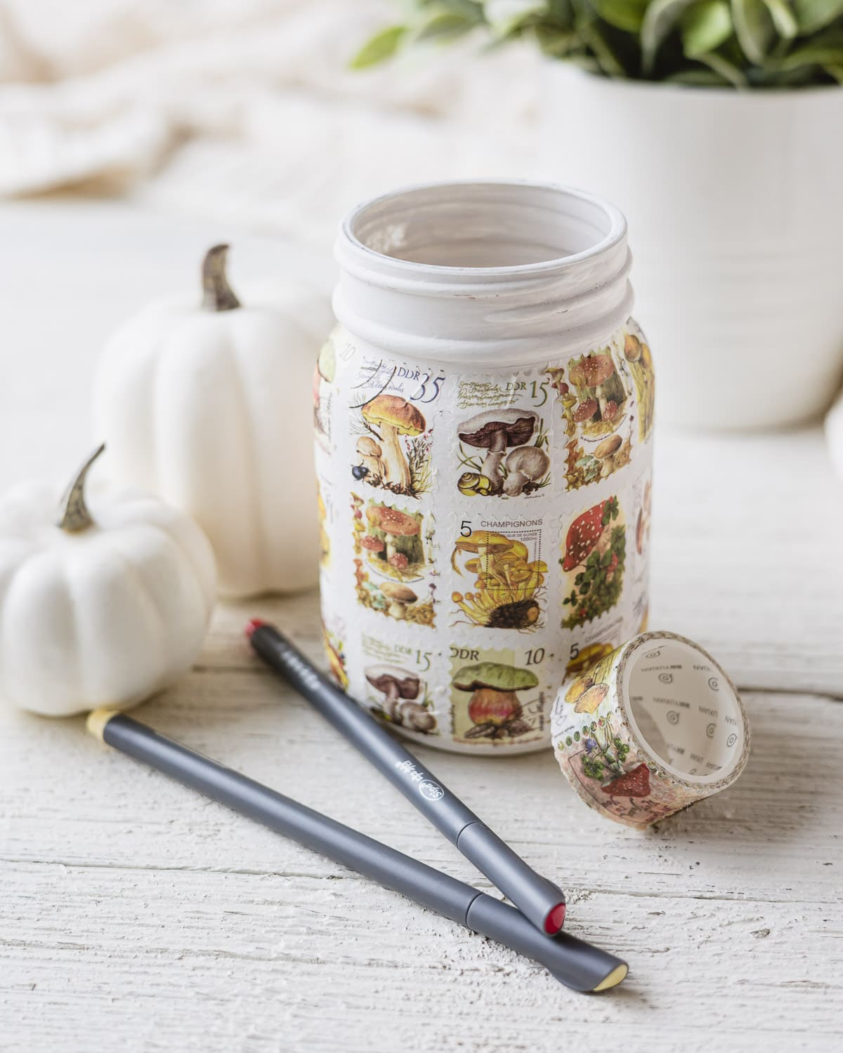 A mason jar covered with postage stamp style washi tape with faux pumpkins in the background.