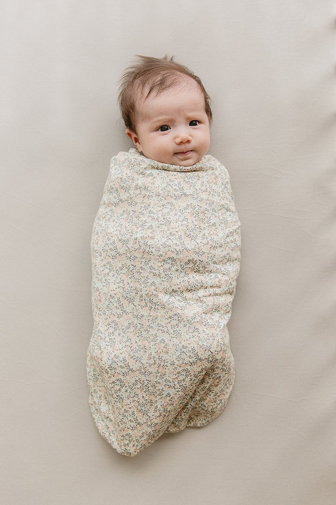 A baby wrapped in a floral swaddle blanket.