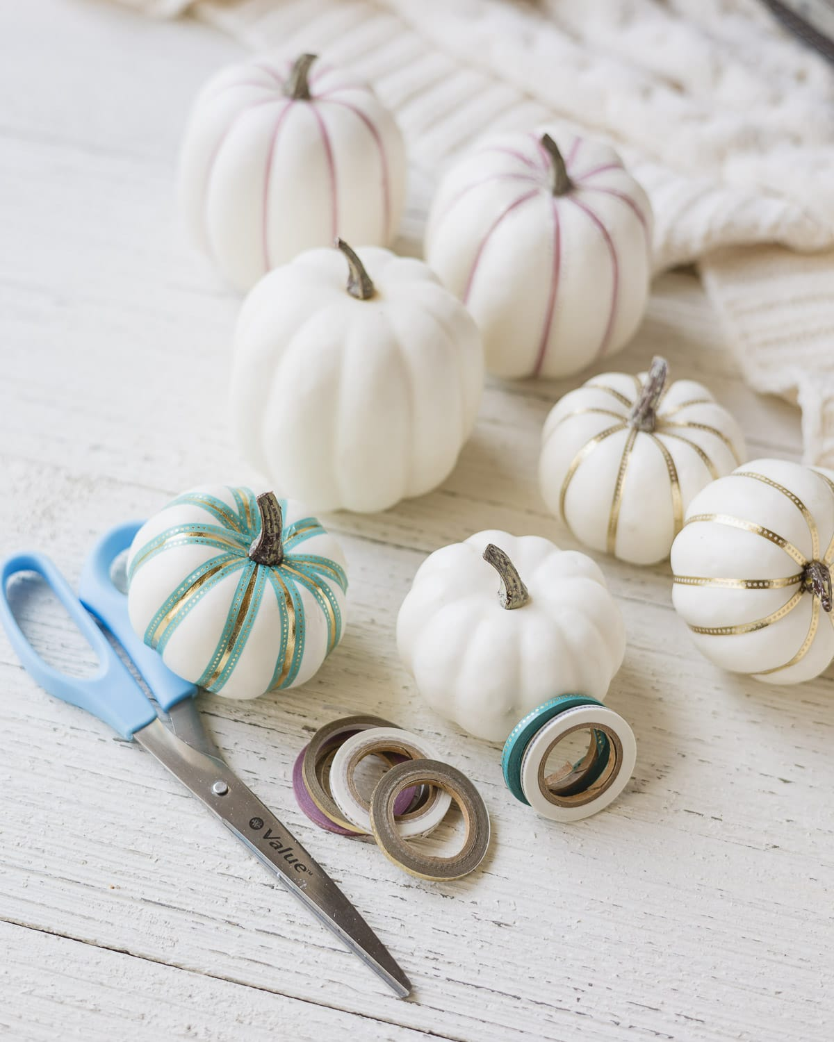 White foam pumpkins, scissors, decorative tape, and decorated pumpkins on a wooden surface.