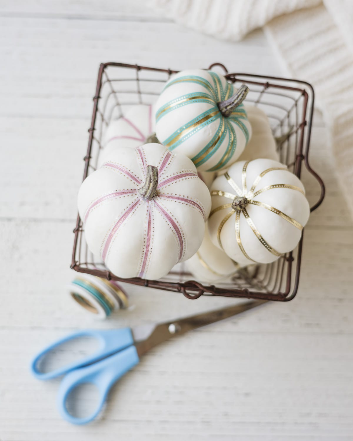White foam pumpkins decorated with colorful washi tape and arranged in a metal basket.