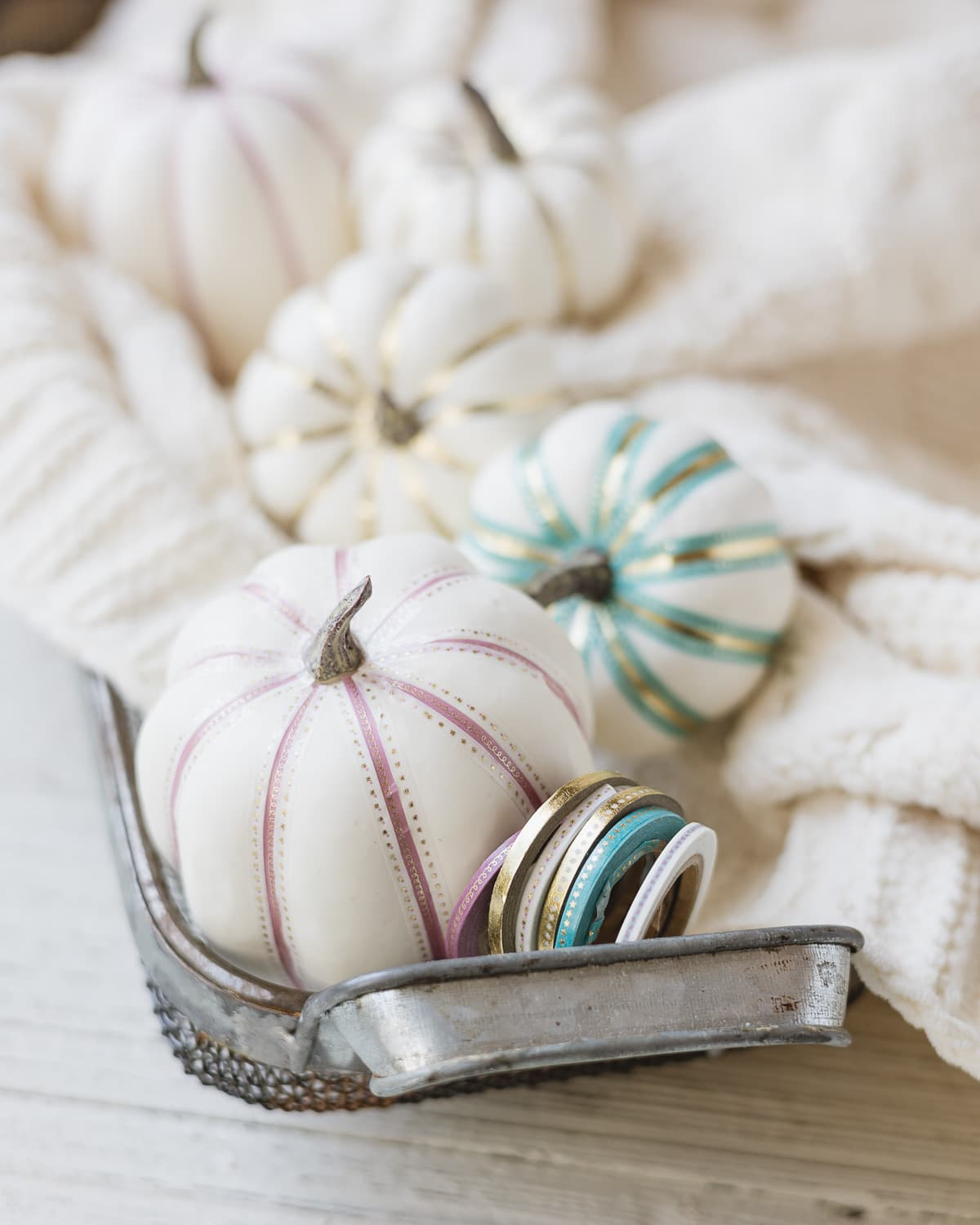 White faux pumpkins decorated with thin washi tape and arranged in a metal basket.