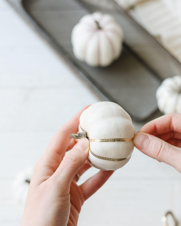 Wrapping gold washi tape around a white foam pumpkin.