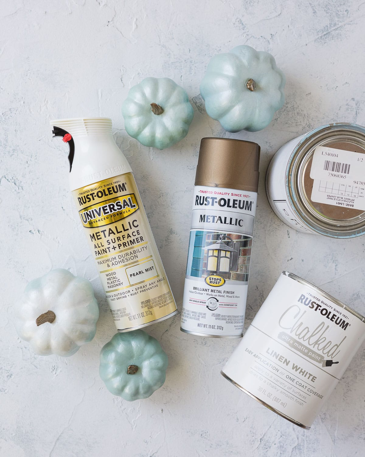 Spray paints, chalk paint, and DIY chalk painted pumpkins on a rustic surface.