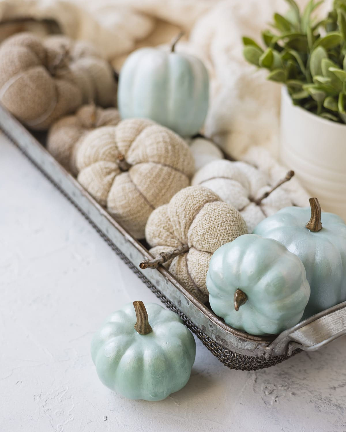 A metal basket filled with handmade home décor pumpkins for fall.