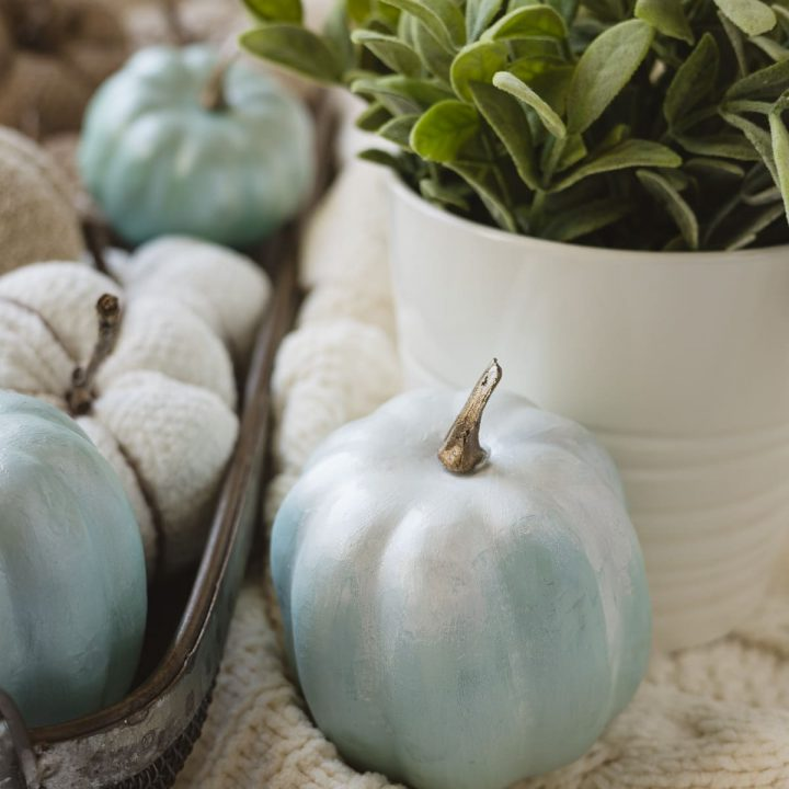A light blue faux pumpkin with a faux plant and a basketful of more pumpkins in the background.